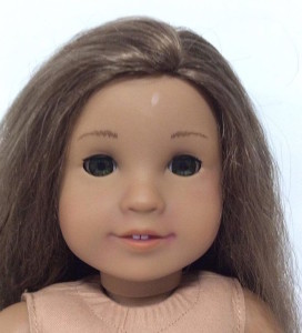 A picture of a Kanani doll. Her hair is dry and she has shine marks and subtle lipstick marks on her face.