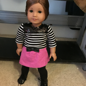 Kanani wearing a striped shirt, pink skirt, black leggings and black boots.