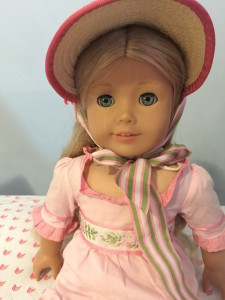 A white doll with blonde hair, aquamarine eyes, a pink regency-style dress and a pink-trimmed straw bonnet.