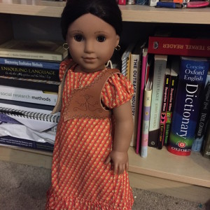A picture of a medium-skinned Latina doll with black hair and brown eyes. She's wearing an orange-patterned dress with a leather vest.
