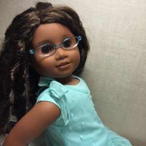 A picture of Lucy, a black doll with curly brown hair and turquoise glasses. She's wearing a light teal dress with a lacy overdress on top.