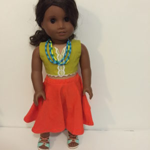 Lucy, a curly-haired black doll wearing a green lace-trimmed top and a bright orange skirt.