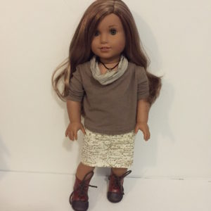Leah, a doll with tanned skin and long caramel-brown hair, wearing a brown slouchy sweatshirt, a skirt with a map print, brown boots and a brown infinity scarf.
