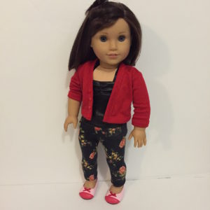 Theo, a brown-haired white doll, wearing a red cardigan, black pleather top, black leggings printed with pink and red roses, and a pair of flats in two shades of pink.