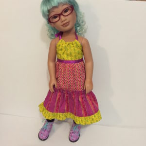 Alice, an East Asian doll with curly turquoise hair, is wearing a bright halter dress made with pink, purple, green and yellow fabric. She's also wearing purple boots with blue and green flowers on them.